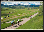 Cyclists and couple walking along the Snowmass Village Golf Course, Aspen, Colorado, USA