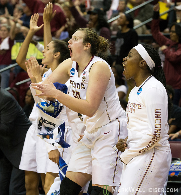 Florida State center Chatrice White (50)  and the bench celebrates after a three point shot during the second half of a second-round game of the NCAA women's college basketball tournament against Missouri in Tallahassee, Fla., Sunday, March 19, 2017. Florida State defeated Missouri 77-55. (AP Photo/Mark Wallheiser)