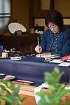 Japanese woman calligrapher writing at a desk Uji, Japan