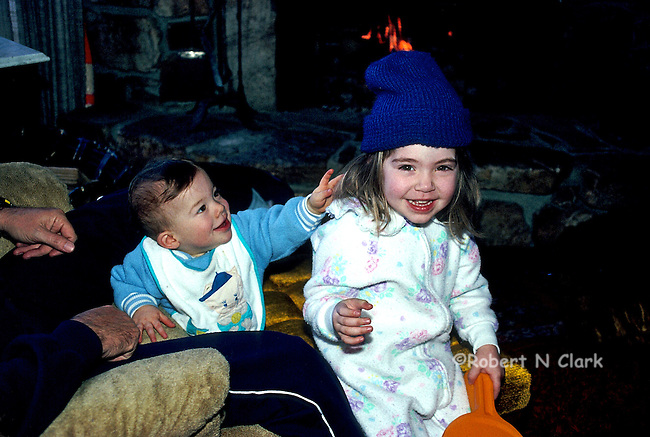 Young boy and girl playing with boy ready to pull wool cap off his sister's head