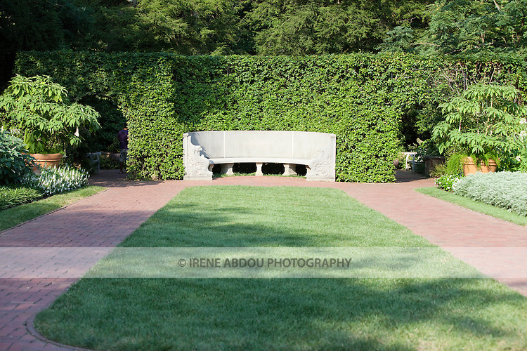 A decorative stone bench sits against a wall of ivy at Longwood Gardens in Kennett Square, Pennsylvania.