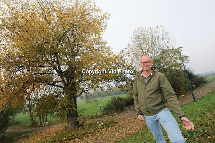 Foto: VidiPhoto<br /> <br /> WOUDRICHEM - Groenbeheerder Henk van der Laan van de gemeente Woudrichem, Rob Vroon, bij een populier langs de dijk bij Woudrichem.