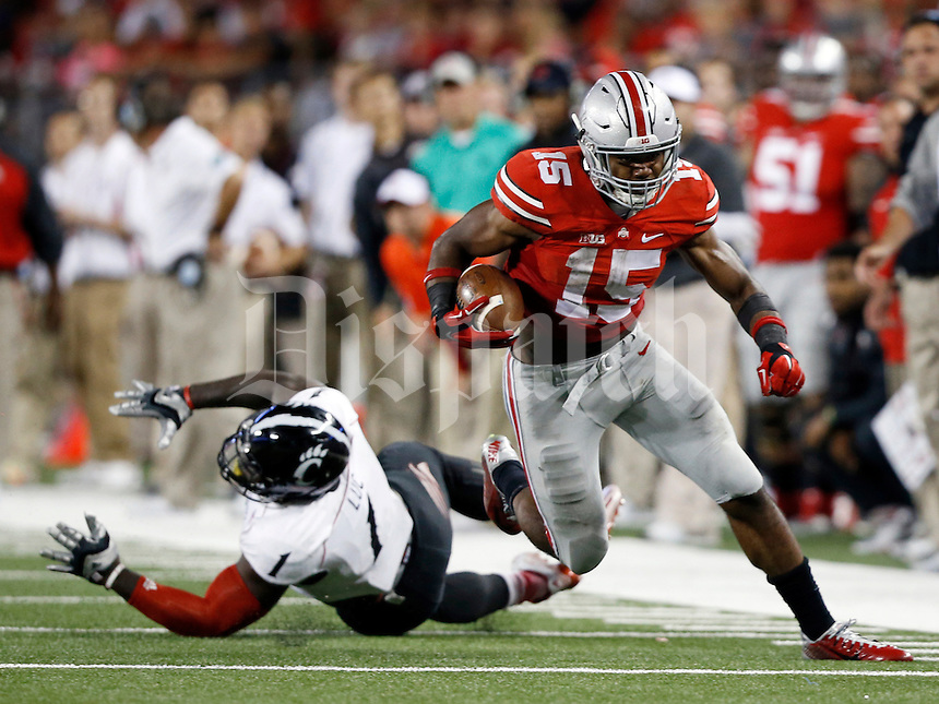 Ohio State Buckeyes running back Ezekiel Elliott (15) rushes for a first down past Cincinnati Bearcats linebacker Jeff Luc (1) during the fourth quarter of the NCAA football game at Ohio Stadium in Columbus on Sept. 27, 2014. (Adam Cairns / The Columbus Dispatch)