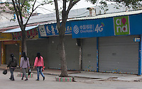 Workers walk past shuttered shops at the edge of the Yue Yuen Industrial Holdings Limited factory in Dongguan, Guangdong Province, China, 03 March 2015.