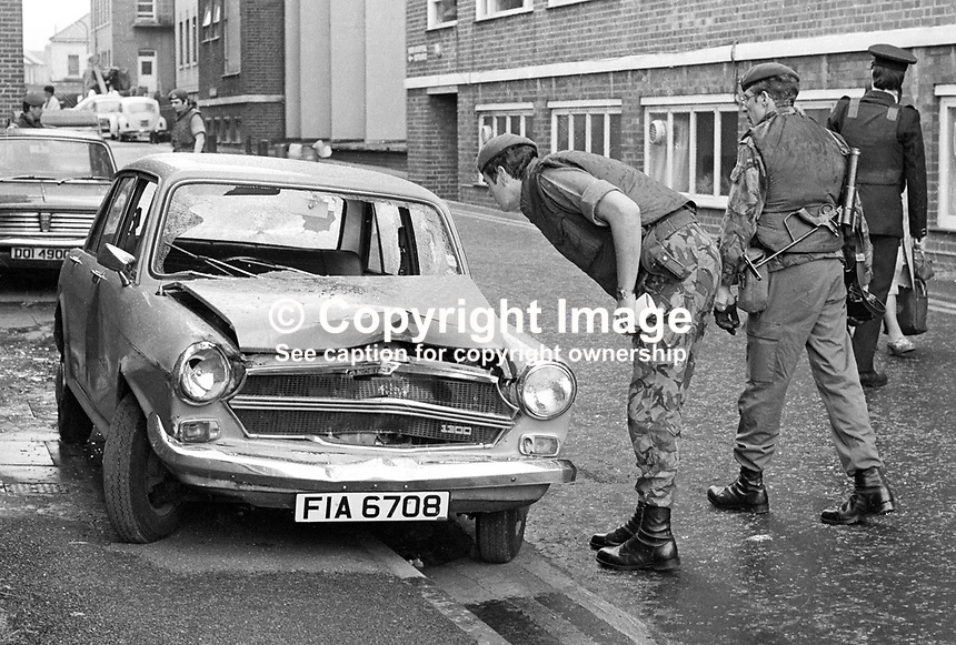 Soldiers and police examine the bullet-ridden crashed car in which a hospital porter coming off duty died at the Royal Victoria Hospital, Belfast, N Ireland, UK, 8th June 1977 in a Provisional IRA gun attack. Gerald Tucker, Belfast, N Ireland, 37 years old, Protestant, was a part-time lance corporal in the Ulster Defence Regiment. 197706080173b<br />
