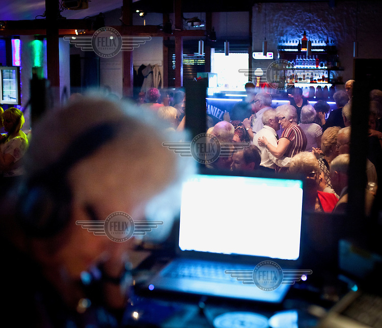 Couples dance as Wika Szmyt, a 74 year old DJ, the oldest in the country, stands at a mixing desk playing music at the Bolek Club. She runs the club night, which is mainly frequented by pensioners, twice weekly.