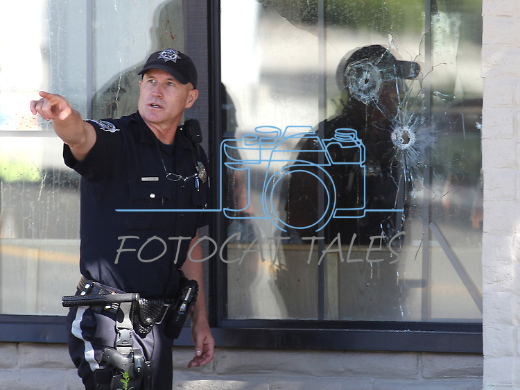 Officers look for evidence near bullet holes into an IHop restaurant in Carson City, Nev., on Tuesday, Sept. 6, 2011, following a shooting that reportedly has left eight wounded and four dead. (AP Photo/Cathleen Allison)