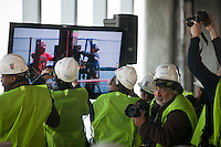 Members of the media photograph a hi-definition video feed from the top of One World Trade Center as a beam is placed becoming the tallest building in New York on Monday, April 30, 2012.  Workers erect steel columns raising the height to over 1,250 feet, a tad above the Empire State Building. When finished the building will be 1,776 feet, the third tallest building in the world. (© Richard B. Levine)