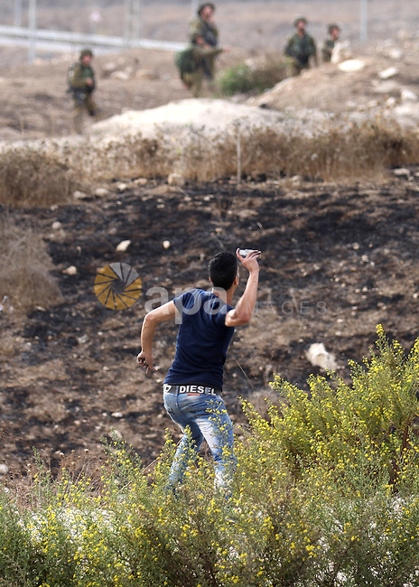 A Palestinian protester throws stones at Israeli security forces during clashes at the Hawara checkpoint, south of the West Bank city of Nablus, on October 13, 2015. A wave of stabbings that hit Israel, Jerusalem and the West Bank this month along with violent protests in annexed east Jerusalem and the occupied West Bank, has led to warnings that a full-scale Palestinian uprising, or third intifada, could erupt. The unrest has also spread to the Gaza Strip, with clashes along the border in recent days leaving nine Palestinians dead from Israeli fire. Photo by Nedal Eshtayah