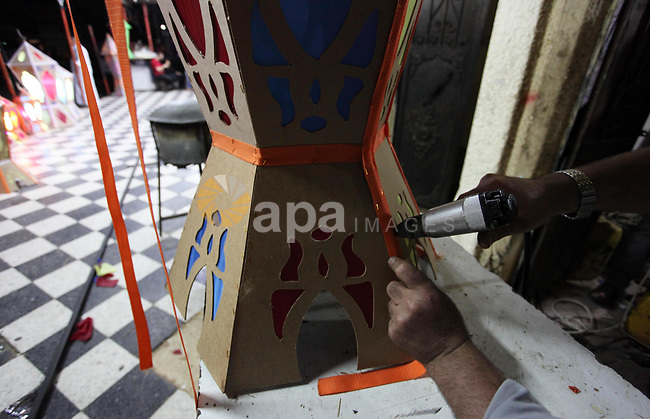 """A Palestinian man manufactures a traditional Ramadan lantern known as """"Fanous"""" in Arabic, at his workshop ready for the month of holy Ramadan in Gaza City on May 13, 2018. Photo by Mahmoud Ajour"""