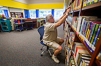 NWA Democrat-Gazette/JASON IVESTER <br /> Rob Dean, library assistant, shelves books on Tuesday, Aug. 18, 2015, in the school's new media center at T.G. Smith Elementary School in Springdale.