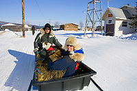 Iditarod air force pilot Danny Davidson and *Teacher on the Trail* Kim Slade sit with 5 dropped dogs in a sled being towed to the airport at Kaltag