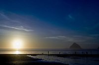Beachcombers wal at low tide and sunset at Oceanside on the Oregon Coast, in front of a sea stack known as Arch Rock (Three Arch Rocks).