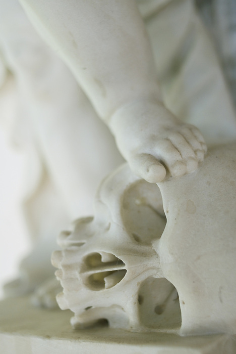 A detail of a marble statue, showing the foot of a cherub resting on a skull.