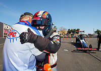 Jan 31, 2018; Chandler, AZ, USA; NHRA top fuel driver Steve Torrence prays with an RFC chaplain during Nitro Spring Training Testing at Wild Horse Pass Motorsports Park. Mandatory Credit: Mark J. Rebilas-USA TODAY Sports