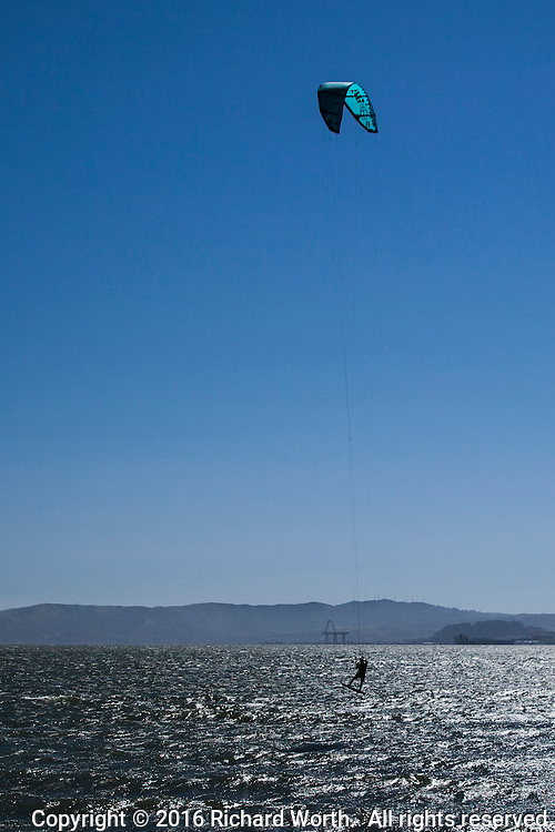 A kiteboarder hangs from his harness attached to his kite,which has lifted him well above the waters of San Francisco Bay along Crown Memorial State Beach in Alameda, California.