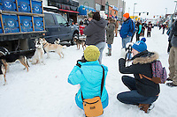 Onlookers photograph a team on 4th avenue prior to the ceremonial start of the Iditarod sled dog race in downtown Anchorage Saturday, March 2, 2013. ..Photo (C) Jeff Schultz/IditarodPhotos.com  Do not reproduce without permission