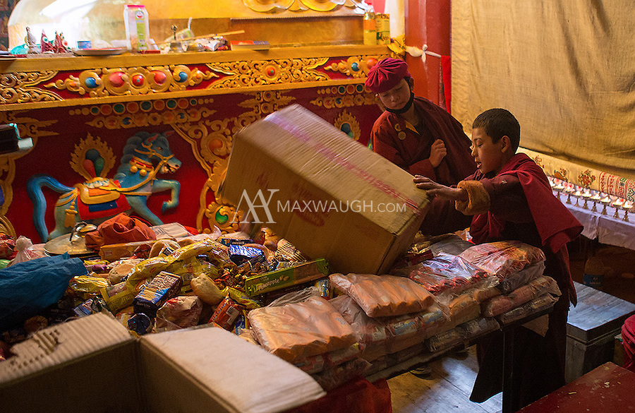 Young monks dump candy and sweets left as tributes in the Hemis Monastery.