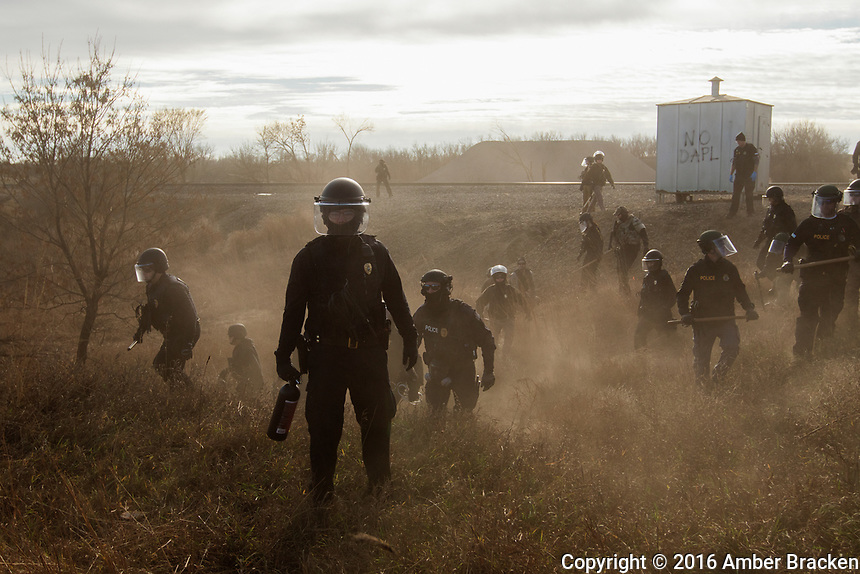 Morton County Sheriffs - Riot police clear marchers from a secondary road outside a Dakota Access Pipeline (DAPL) worker camp using rubber bullets, pepper spray, tasers and arrests. In other incidents they've employed militarized vehicles, water canons, tear gas and have been accused of using percussion grenades.