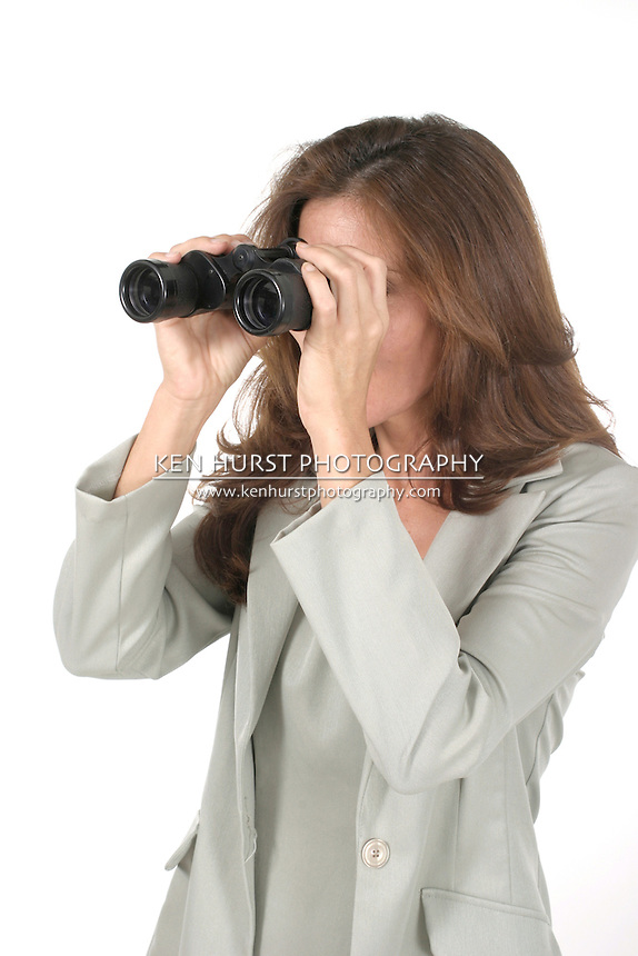Beautiful, attractive woman looking through binoculars; Shot on white