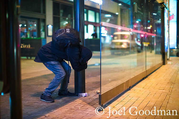 © Joel Goodman - 07973 332324 . 07/04/2017 . Manchester , UK . A man , believed to be suffering the effects of Spice , stands still bent over whilst gripping on a to a pole in the street for support , in Piccadilly . Greater Manchester Police have authorised dispersal powers and say they will ban people from the city centre for 48 hours , this evening (7th April 2017) , in order to tackle alcohol and spice abuse . Photo credit : Joel Goodman