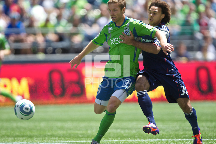 Seattle Sounders FC defender Jeff Parke and New England Revolution defender Kevin Alston battle for the ball at .CenturyLink Field in Seattle Sunday June 26, 2011. The Sounders won the game 2-1.   during play between the Seattle Sounders FC and the New England Revolution at .CenturyLink Field in Seattle Sunday June 26, 2011. The Sounders won the game 2-1.