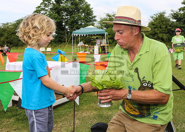 2014 World Championship Snail Racing in Congham (Norfolk)<br /> Picture Description:<br /> Zeben Butler-Alldred, aged 5, from London redeive the coveter prize.<br /> The 2014 championships were held on 19th July 2014 and the winner was a snail called Wells owned and trained by Zeben Butler-Alldred, aged 5, from London.&nbsp; Wells completed the course in 3 minutes 19 seconds, a slow time because of the heat. Zeben was on holiday in West Norfolk and named his snail after the local town Wells which he liked.<br /> General info:<br /> For more than 25 years the World Snail Racing Championships have been held at Congham, near King's Lynn, in Norfolk.Before snails can enter a race a sticker with a number must be put on so they can be identified. The snails race from the centre of a circle to the outside. The circle has a radius of 13 inches. The snails are put in the middle and pointed in the right direction.The  Snail Master Neil starts the races. He shouts: &quot;Ready, steady, SLOW!&quot; And off dash the snails! The Snail Master keeps the course well-watered as snails like damp conditions.Races are held on a table covered with a white cloth. Machine a circle, with braid in the middle, and then machine a similar circle 13 inches away.Owners do dress up. The World record stands at 2 minutes over the 13 inches. It was set up in 1995 by a snail called Archie. The record can only be challenged at the World Championships at Congham.Giant foreign snails are not allowedOften owners like to give their snails names like Speedy or Schumacher!<br /> Picture by Marcello Pozzetti &copy; IPS PHOTO AGENCY<br /> Cavell Barn<br /> The Common<br /> Swardeston<br /> Norwich<br /> Norfolk<br /> NR14 8DZ<br /> T 01508 571 480<br /> M 07973308835