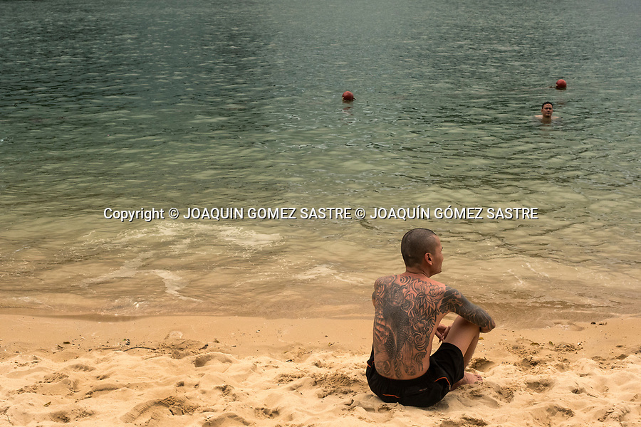 A young man with tattoos enjoys one of the many beaches in Halong Bay<br /> HALONG-VIETNAM