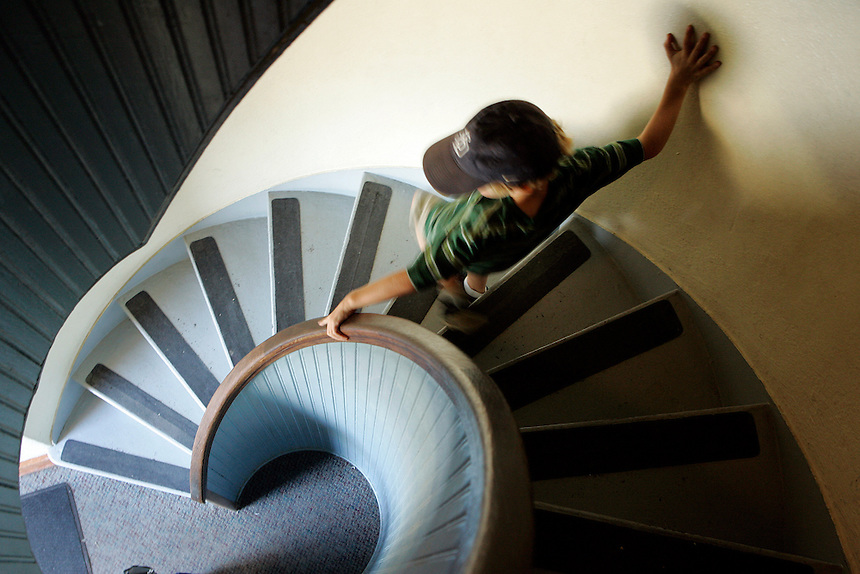 A young boy on the spiral staircase at the Cabrillo National Monument Lighthouse on Point Loma, San Diego, California.