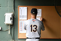 Manager Patrick Osborn (13) of the Charleston RiverDogs places the lineup on the bulletin board before a game against the Greenville Drive on Thursday, July 27, 2017, at Fluor Field at the West End in Greenville, South Carolina. Charleston won, 5-2. (Tom Priddy/Four Seam Images)