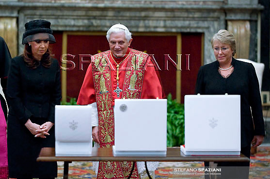 Chilean President Michelle Bachelet Jeria (R) and Argentine President Cristina Fernandez de Kirchnerat (L) exchange gifts with Pope Benedict XVI (C) during their private audience at the Vatican on November 28, 2009.
