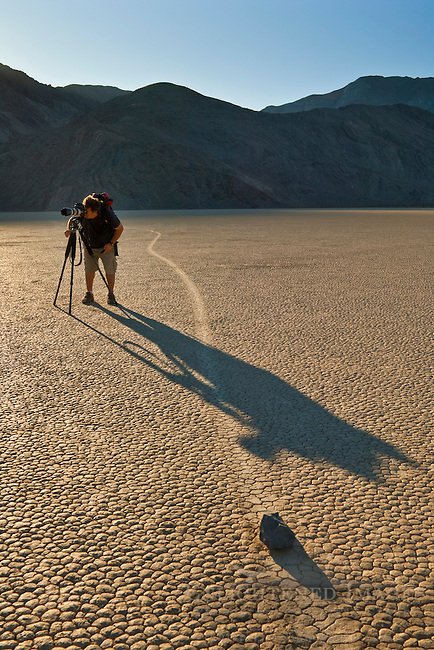 Photographer next to tracks left by mysterious moving rocks on the dried flat mud at the Racetrack Playa, Death Valley National Park, California