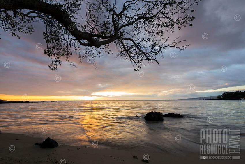 Gentle waters reflect the setting sun under passing storm clouds over Mauna Kea Beach, South Kohala, Big Island.