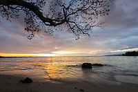 Gentle waters reflect the setting sun under passing storm clouds over Mauna Kea Beach, South Kohala, Big Island.