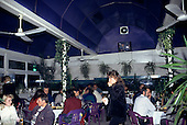 Varna, Bulgaria. People sitting in a modern restaurant eating and drinking; purple plastic chairs and ceiling.