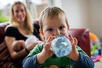 A little boy drinks from a bottle of water while his mother is  breastfeeding her 2 month old baby daughter in the background.<br /> <br /> Hampshire, England, UK<br /> 10/02/2013