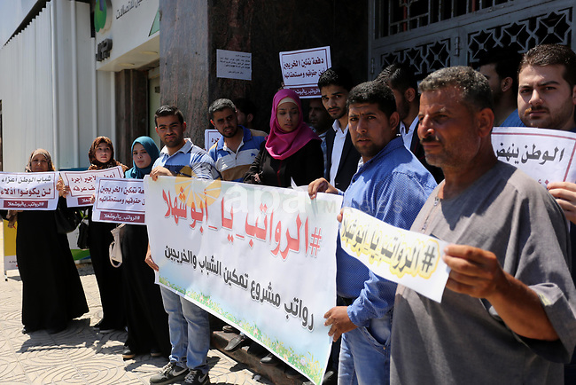 Palestinian graduates who work at temporary projects hold placards during a protest to demand their salaries, in front of Bank of Palestine in Gaza city on June 18, 2017. Photo by Ashraf Amra