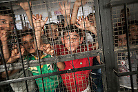 June 08, 2015 - Bekaa Valley, Lebanon: Syrian refugee children are seen behind a fence during a break at the evening shift in Qoub Elias elementary school. (Photo/Narciso Contreras)