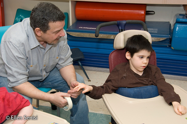 MR / Albany, NY.Langan School at Center for Disability Services .Ungraded private school which serves individuals with multiple disabilities.Teaching assistant holds childs' hand and talks to him is seated in a Rifton chair. Boy: 8, cerebral palsy, spastic quadriplegic, nonverbal with expressive and receptive language delays.MR: Hac2; Sai2.© Ellen B. Senisi