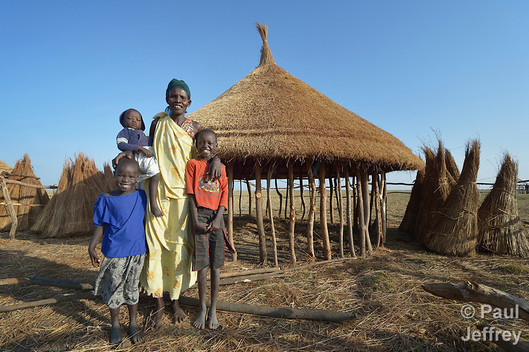 Adhieu Deng Ngewei and three of her children pose in front of their new hut on April 12, 2017, in Dong Boma, a Dinka village in South Sudan's Jonglei State. They and most other families here recently returned home after being displaced by rebel soldiers in December, 2013, and they face serious challenges in rebuilding their village while simultaneously coping with a drought which has devastated their cattle herds.<br /> <br /> During the period they were displaced, this family took refuge on an island of the White Nile River, living on the edge of starvation for almost three years.<br /> <br /> The Lutheran World Federation, a member of the ACT Alliance, is helping the villagers restart their lives with support for housing, livelihood, and food security. The ACT Alliance funded the construction of this family's new hut.