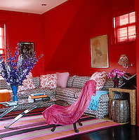 Bright red walls set the tone for this vivid living room, in which the sectional sofa's upholstery and flower-print pillows are by Roberta Roller Rabbit