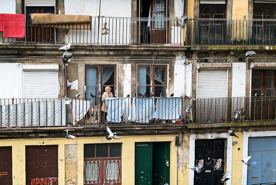A woman feed pigeons outside her home in Oporto, Portugal.