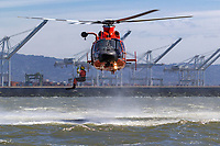 A USCG Swimmer jumps into the waters of San Francisco Bay from a hovering MH-65 Dolphin helicopter.