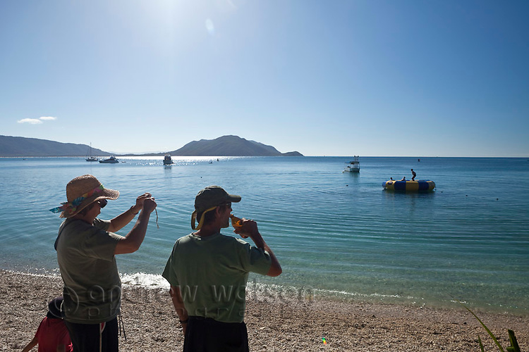 Couple looking out over clear waters of Welcome Bay.  Fitzroy Island National Park, Cairns, Queensland, Austtralia