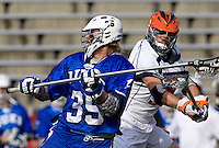 Wyatt Melzer (28) of Virginia checks the ball away from Parker McKee (35) of Duke during the ACC men's lacrosse tournament semifinals in College Park, MD.  Virginia defeated Duke, 16-12.