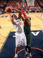 Virginia forward Anthony Gill (13) shoots next to Miami forward Raphael Akpejiori (4) during an NCAA basketball game Saturday Feb, 24, 2014 in Charlottesville, VA. Virginia defeated Miami 65-40.