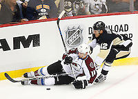 Ben Lovejoy #12 of the Pittsburgh Penguins reaches underneath Blake Comeau #14 of the Colorado Avalanche for the puck in the first period during the game at Consol Energy Center on November 19, 2015. (Photo by Jared Wickerham/DKPittsburghSports)