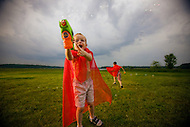 A young boy with glasses aims his bubble gun at the camera and fires.