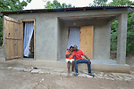 Darima Marie Motte and her husband Riccin Cherichel sit together on the porch of their new home in Lareserve, a village near Jean-Rabel in northwestern Haiti. The family's previous house was destroyed during Hurricane Matthew in 2016, and Church World Service, a member of the ACT Alliance, helped the family build their sturdy new home.