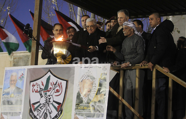 Palestinian President Mahmud Abbas lights a flame as thousands of Palestinians look on, on the eve of the 48th anniversary of the formation on the Fatah movement, on December 31, 2012, in the West Bank city of Ramallah. The Fatah anniversary commemorates the first operation against Israel claimed by its armed wing then known as Al-Assifa (The Thunderstorm in Arabic) on January 1, 1965. Photo by Issam Rimawi